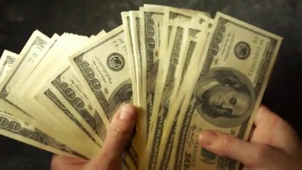 Female hands show a stack of 100 dollar bills.