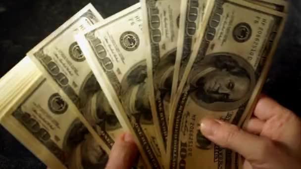 Ženské ruce spočítat pack 100 dolarové bankovky. Zvětšení obrazu v pohybu.