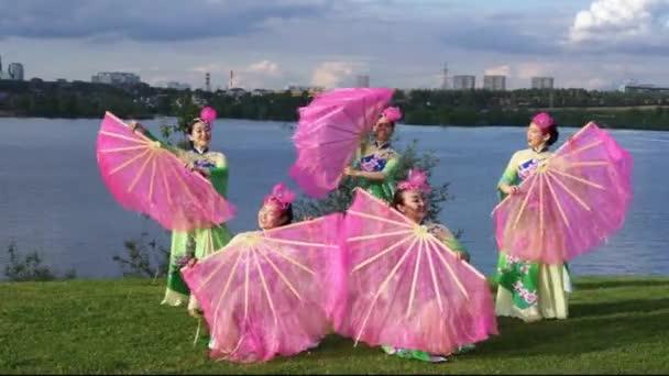 Gruppe von fünf asiatischen Schauspielerinnen in traditionellen chinesischen Kostümen mit Fans, die am Flussufer im Freien tanzen