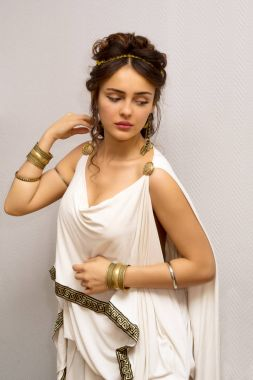 portrait of a beautiful graceful greek young woman in a traditional antique white tunic