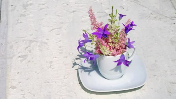 Astilba and blue bell flowers bouquet in a white coffee cup as a vase develop in the wind on an old white background with copy space for your text