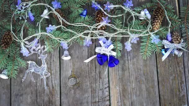 Vánoční rámeček z jedle strom větví, věnce, kužely, zvony a sobů hračky na dřevěný stůl. pohled shora s kopií prostor pro váš text. Blikající vánoční věnec