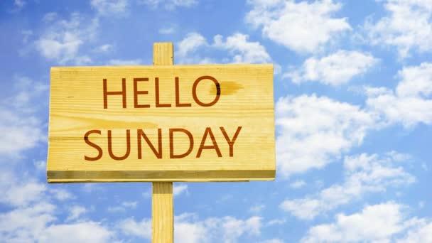 Hello vasárnap. Szöveg-ra-a fából készült jele ellen idő telik el a kék ég felhők.