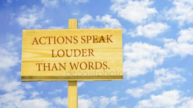 Actions speak louder than words. Words on a wooden sign against time lapse clouds in the blue sky.