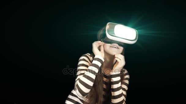 Dospívající dívka pomocí Vr headsetu. Veselá dívka usmívající se Kavkazská ve virtuální realita brýle a gestikuloval rukama s mnoha různých emocí od strachu k údivu