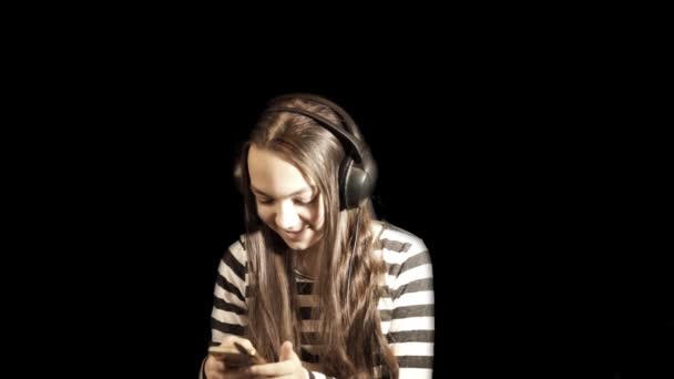 Teenager girl listens to music in headphones and gestures dancing. Close up portrait against a black background