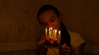 Teenager 12 year old caucasian girl holding small birthday candles in darkness and blowing it out.