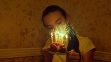 Teenager 12 year old caucasian girl holding small birthday cake with candles in darkness and blowing it out. Glittering magic flour animation above the cake.