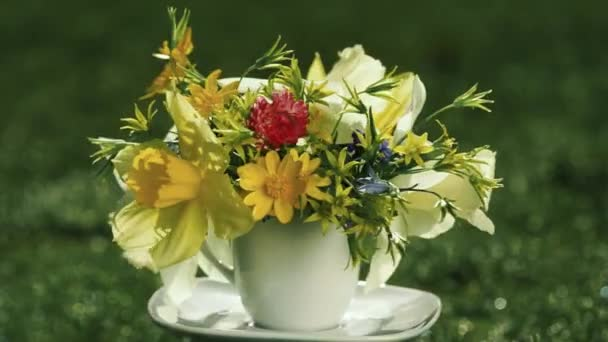 yellow narcissus and wild spring flowers bouquet in a coffee cup instead of vase rotating in the blurred grass background