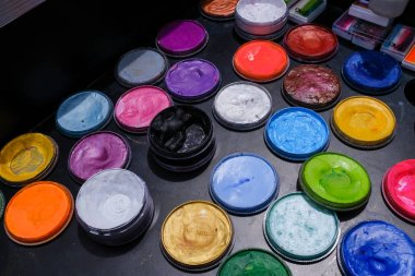 colorful paint cans on black color table closeup view