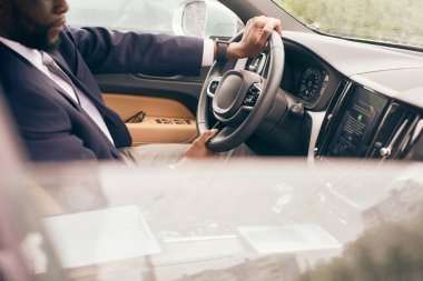 Businessman in a suit sits in a car and holds steering wheel.
