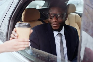 Businessman in a suit sits in a car in the drive-through.