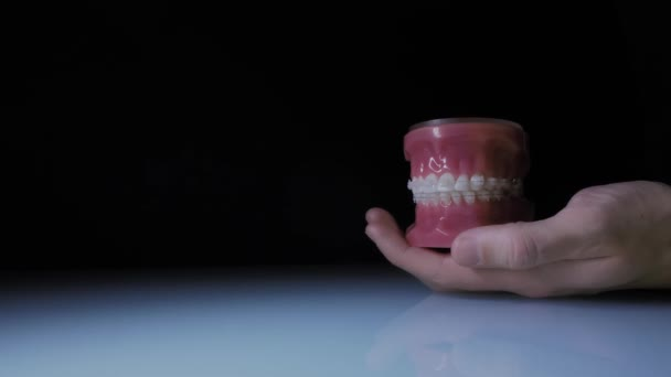 Close-up of teeth with transparent braces. Demonstration of the jaw with braces in the doctors hand.
