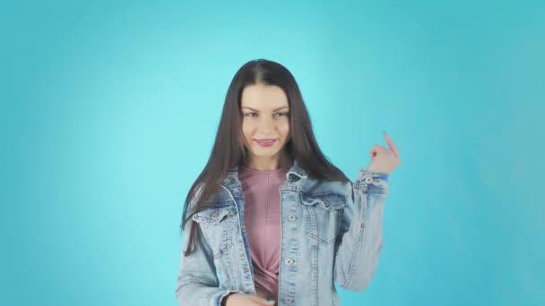Fiatal vicces barna egy farmer kabát táncok és mosolygós elszigetelt kék