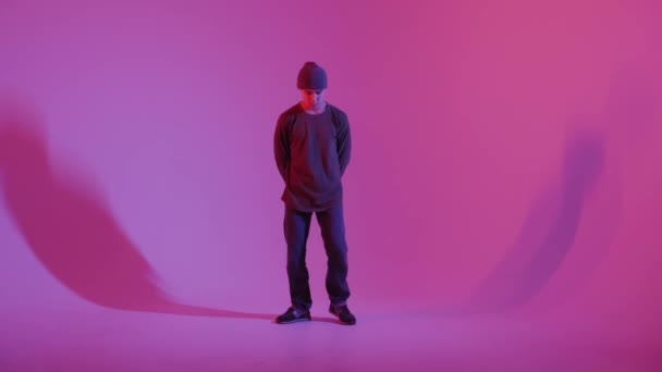 Young Man in a Jumper Dancing Contemporary Dance in Studio. Breakdancing. Dance School Poster. Copy Space. Battle competition announcement. Pink and Blue Background.