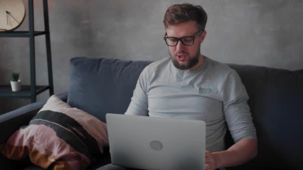 Fiatal szakállas férfi szemüveggel egy laptopon dolgozik. Szabadúszó.