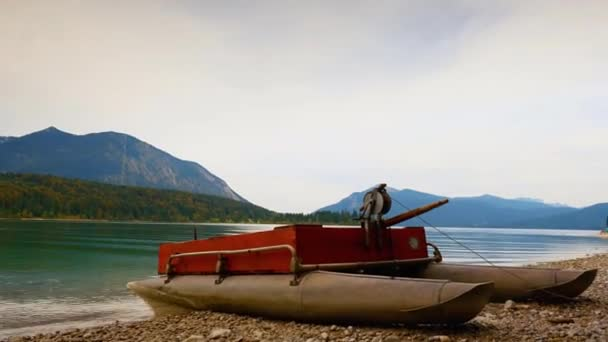Časosběrné video. Zvedl pohled nad malou lodí na oblázkové pobřeží, zrcadlo ve vodě horského jezera. Jemné vlny na podzimní hladiny vody, ostrovy les a vysoké hory v pozadí
