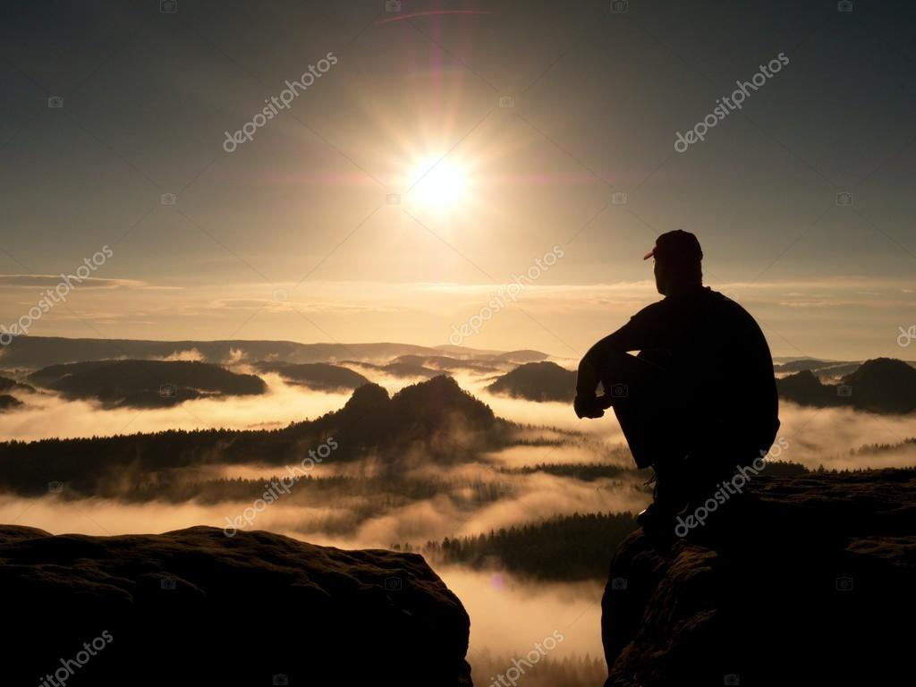 Moment de solitude. Homme au chapeau assis au sommet du rocher et regarder  dans coloré brumes et du brouillard dans la vallée de la forêt. 8915679e80a