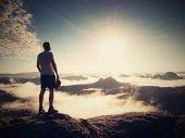 Természetjáró silhouette állva sziklás csúcs, ködös-völgy felett.
