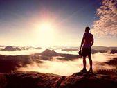 Ember marad a sziklás csúcs piros sapkát. Férfi séta át a sziklás csúcs növekvõ szép pillanat a természet csodája. Vintage effect