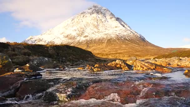 Sunny winter day on meadow at river Coupall at delta to river Etive. Snowy cone of mountain Stob Dearg 1021 metres high. Higland in Scotland an marvelous day. Dry grass and heather bushes on banks.