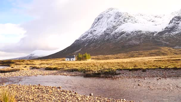 The river Coupall at delta to river Etive below snowy cone of mountain Stob Dearg 1021 metres high. Climbers base camp cottage. Higland in Scotland an marvelous sunny winter day. Dry grass.
