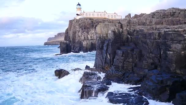 Gyönyörű Neist Point világítótorony-nyugati partján, a skóciai Skye szigetén-egy viharos naplemente alatt. Shinning világítótorony áll a Hebridák-tenger felett, a hullámok ostromolják a rock és a szikla.