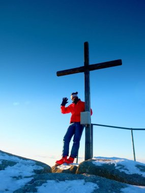 Man hiker in warm clothes on summit  with wooden cross.