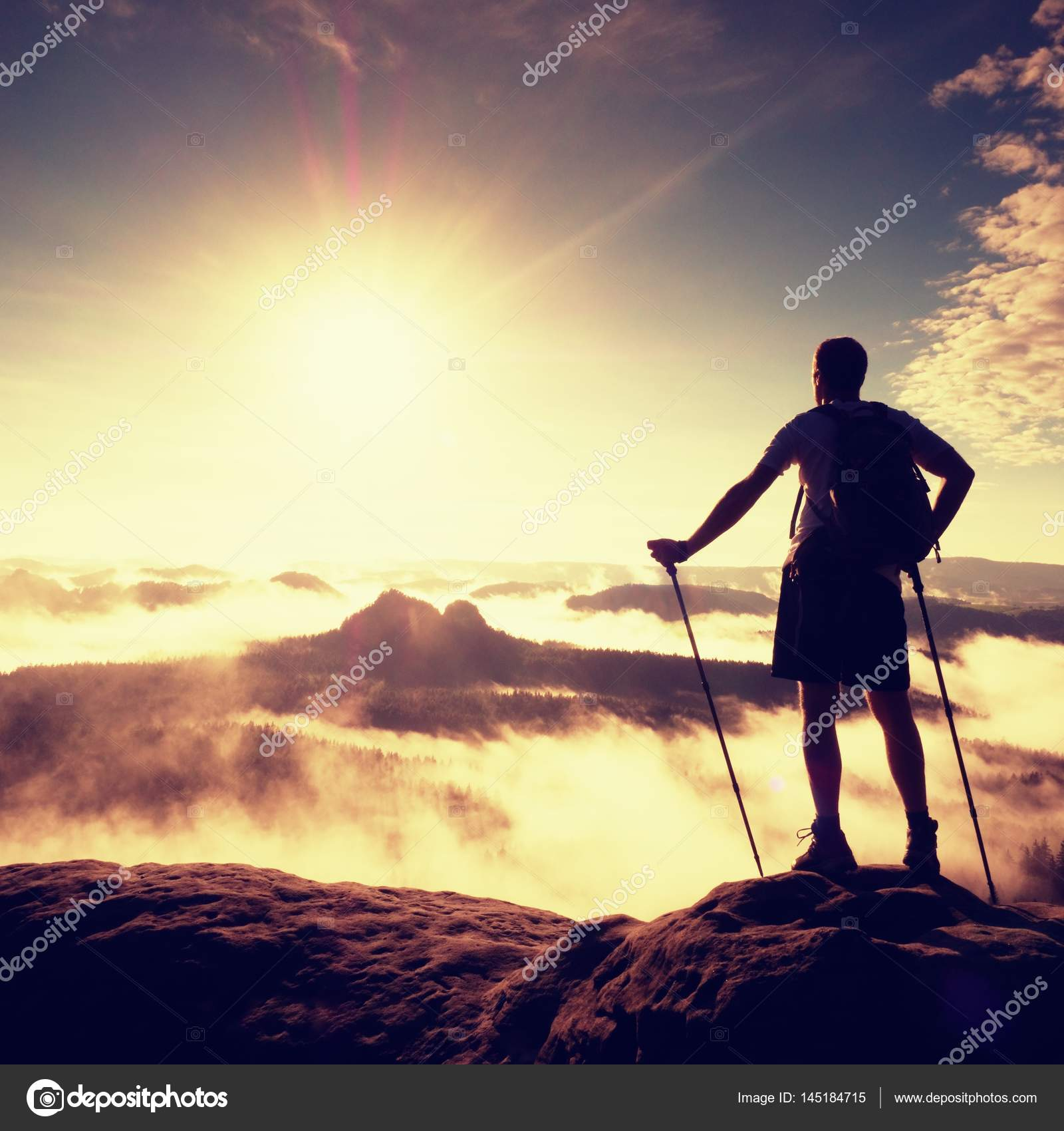 Tall backpacker with poles in hand  Sunny misty daybreak in rocky
