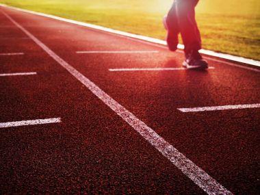 Sportsman on running stadium racetrack. Adult in evening training