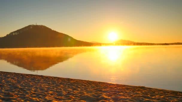 Vysoký sportovec tlačí kolo v mokrém písku horské jezero pláž, barevný západ slunce oblohou v pozadí a reflexe v hladké hladiny vody