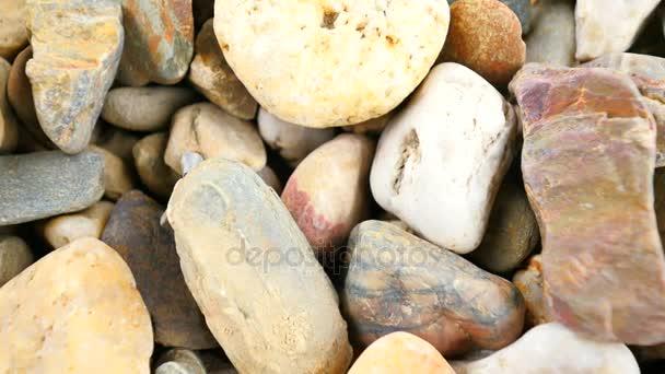 Staré kamenné dlažby z přírodní štěrk, suché oblé kameny, tradiční stavební materiály, malé barevné oblázky. Kamerou pohybující se zblízka na zem