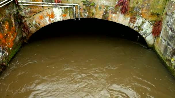 Vody z toku říčka do malé kamenité tunelu nebo mostu. Hnědá kalné vody se stíny a reflexe... Kamenné stěny jezu