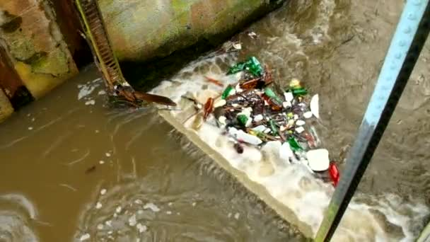 Zpomalený pohyb. Plastové lahve a další nepořádek na hladiny vody. Odbočka ze špinavé vody nad jez na malé řece s bahnité vody. Kamenná stěna jezu