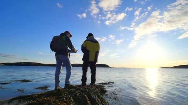 Kamarádi mluví o rybaření a pěší turistiky. Muž mladý rybolov na moři mluvit s člověkem tramp s trekingových holí a zelené sportovní batoh. Muži si užívat rybaření s krásný západ slunce