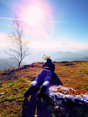 Man lay down and taking photo by mirror camera on neck. Snowy rocky peak of mountain.