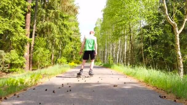 Zadní pohled na inline bruslař v zelené běžící tílko. Venkovní inline bruslení na hladké asphal v lese. Světlé kůži člověka kop do šišky na silnici, s těžištěm.