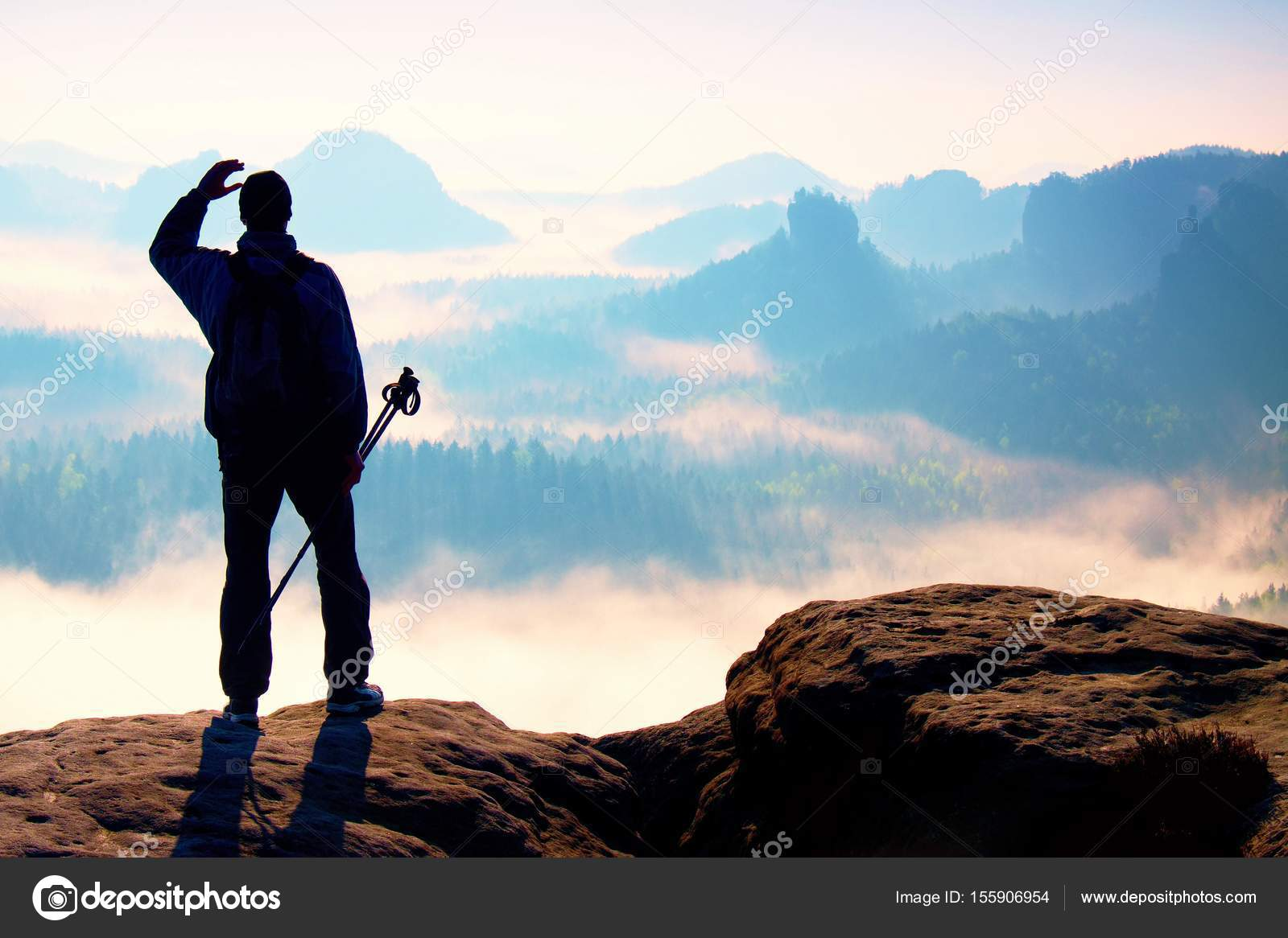 Misty day in rocky mountains  Silhouette of tourist with poles in