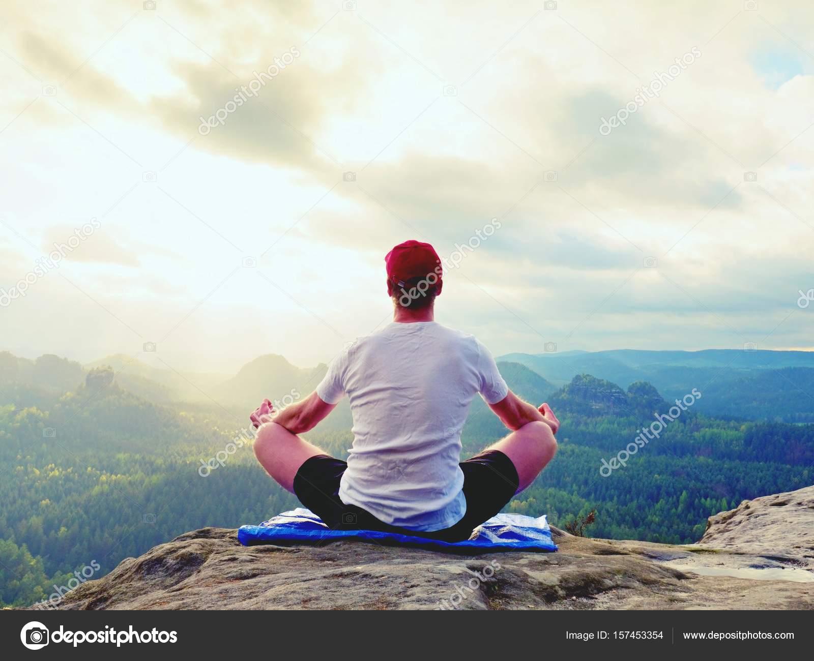Assis seul pose de Yoga pratiquant l homme sur le piton rocheux. L homme  dans le matin brumeux faire méditation et profitant de la vallée de vie —  Image de ... 5f308cfdc3c