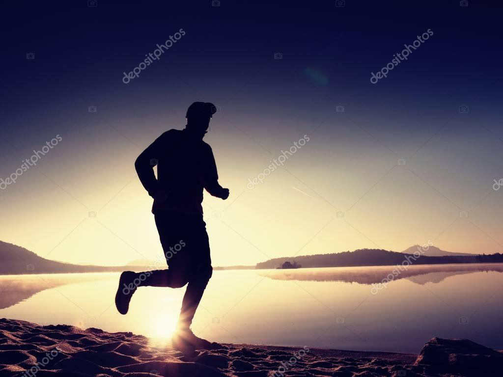 man exercising  and stretching on the lake beach at sunrise. Healthy lifestyle. Alone young fitness man exercise  at morning beach