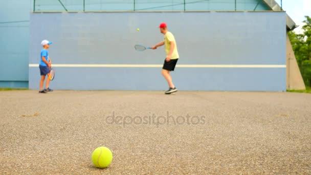 Otec a syn Začínaltak trénovat na tréninkové zdi. Hobby hráče s raketou a hrát na hřišti míč