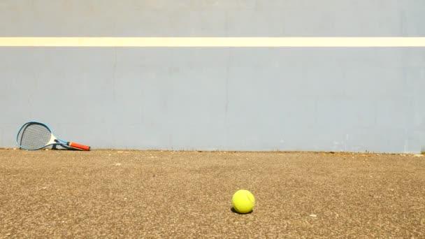 Prázdné trénink tenisový kurt s modrým skákací tenisová zeď. Staré žluté koule je skákání na základě špatné asfaltu
