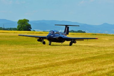 Memorial Airshow.   Czech L29 advanced jet traning aircraft. Landing at a grassy airport.