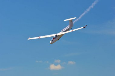 Memorial Airshow. Flying Glider aerobatic team withlight sailplane showing his performance, smoke effect