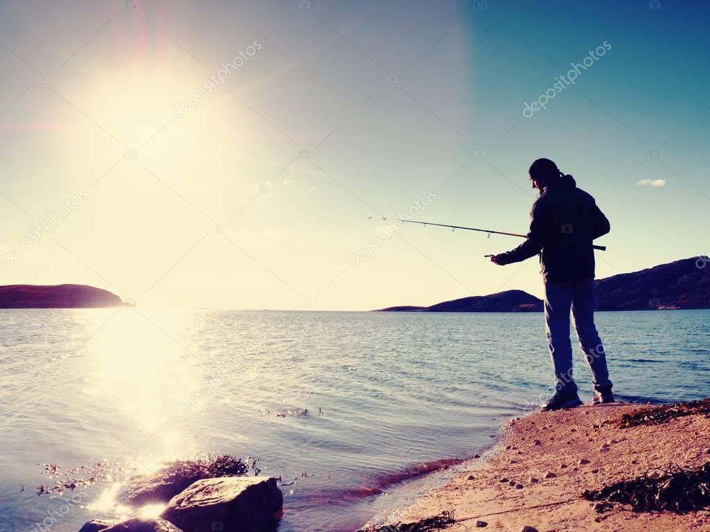 Fisherman check fishing line and pushing bait on the rod, prepare himself and throw lure far into peaceful water.