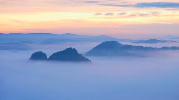 timelapse 30fps. Jaro mlhavé ráno v lesní krajině. Zobrazit okolí. Majestátní vrcholy snížení osvětlení mlha. Hluboké údolí je plné barevné mlhy a skalnaté kopce jsou trčí na slunce