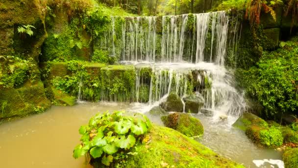 kamenité jezu na malé horské řeky. proud teče přes pískovcové bloky a dělá mléčná voda.