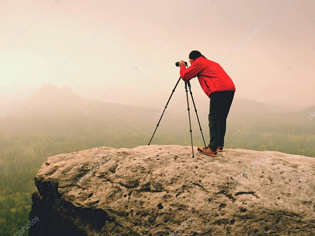Artist stay  with tripod on summit and  takes pictures of autumnal coutryside. Misty landscape