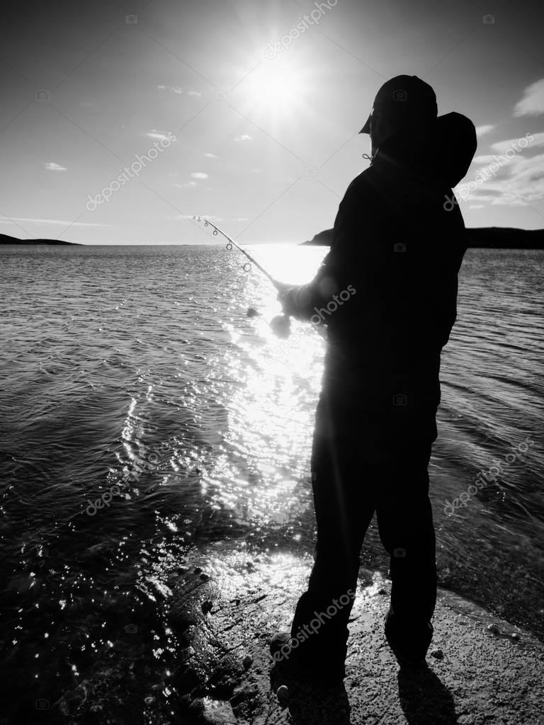 Fisherman check fishing line and pushing bait on the rod. Fisherman silhouette at sunset