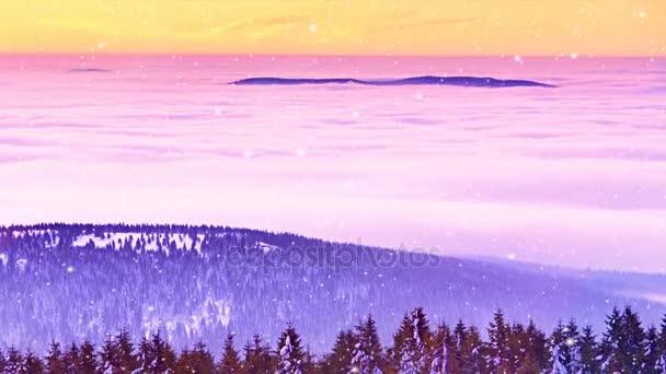 Vánoční ráno sněží zároveň růžová oranžová svítání nad mlhavé zimní hory. Vrcholky hor nad krémové mlha v údolí